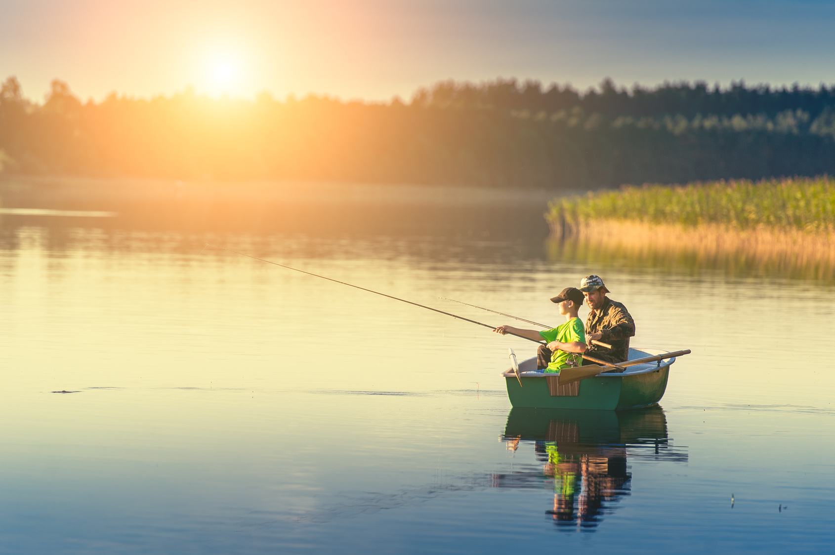 Father and son catch fish from a boat at sunset my westshore for Fishing boat rentals near me
